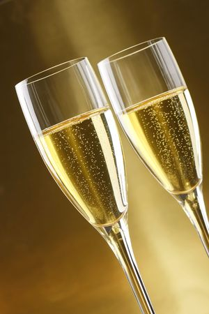 Glasses of champagne with gold background with walnuts, candels and dryed raisins photo