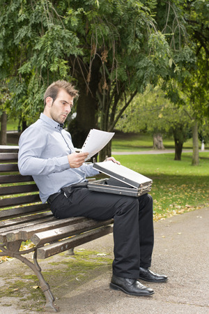 lifestile: Businessman sitting on wood bench in the park and works.