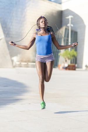 jump rope: Ejercicio Hermosa mujer africana deporte y la formaci�n en la calle, el concepto de estilo de vida saludable. Foto de archivo