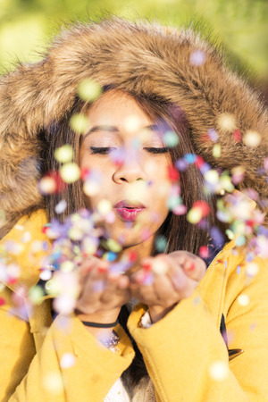 anorak: Closeup portrait of beautiful latin woman blowing confetti in the air, and new year holiday party concept.