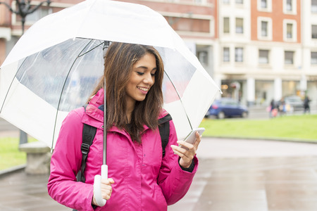 autumn rain: Smiling woman with umbrella using smart phone in the street.