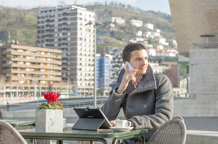 public space: Man laptop computer and talking by phone in public space. Stock Photo