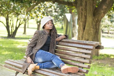 away: Beautiful woman sitting on wood bench looking away, outdoor.