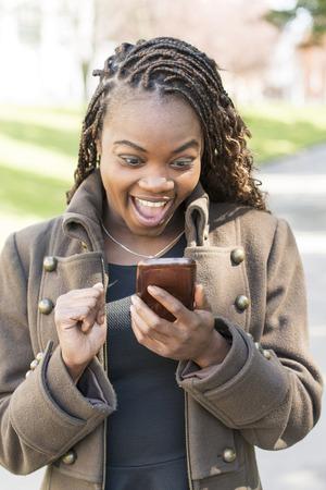 personas hablando: Sonriente mujer mirando a su mensaje de tel�fono inteligente, al aire libre.