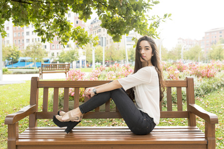 brunete: Elegant woman sitting on bench in the park.
