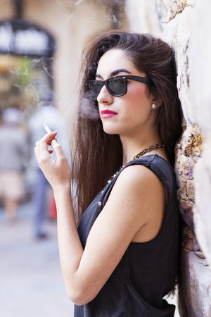 seductive expression: Glamorous brunette woman with sunglasses smoking, retro style.