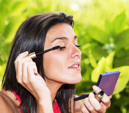 making up: Beautiful girl making up over gren background. Stock Photo