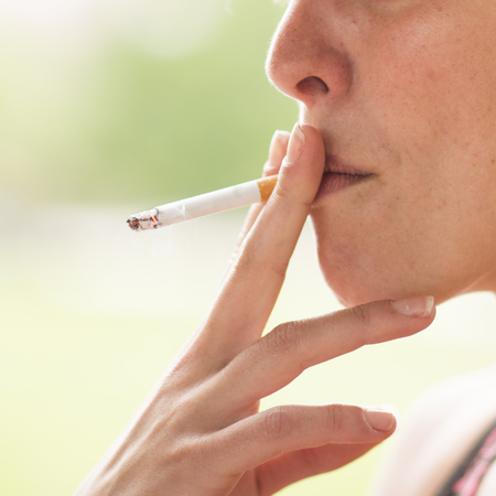 Woman with Exhaling Cigarette Smoke.