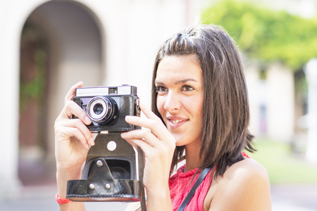 causcasian: Portrait of beautiful woman with retro camera.