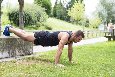 Athletic homme faisant push ups sport en plein air.