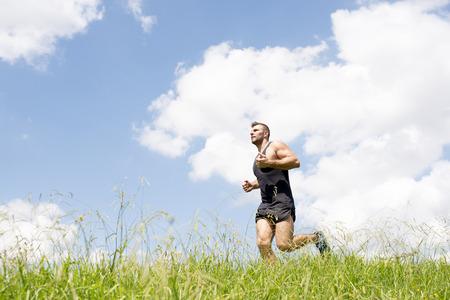 Homme fort athlétique courir sur le terrain.