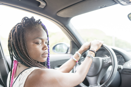 female driver: Beautiful pensive african female driver sitting in the car. Stock Photo