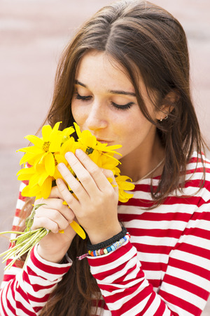 smelling: Portrait of happy girl smelling a bouquet of flowers, outdoor.