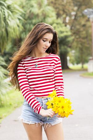 femme romantique: Beautiful romantic woman with flowers bouquet in the park. Banque d'images