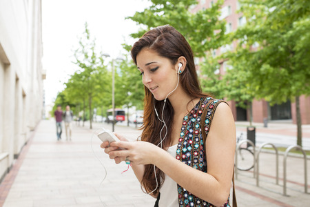active listening: Smiling woman with headphones listening music, in the street. Stock Photo