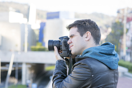 fale: Portrait of photographer with camera in action in the street. Stock Photo