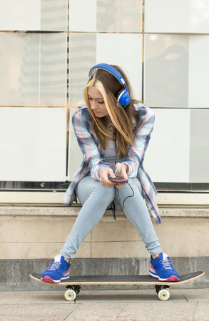 sitting pretty: Urban portrait beautiful girl listening music with headphones in the street.