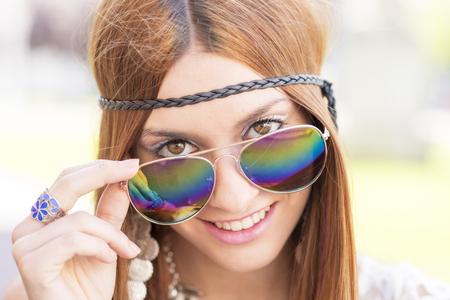 mujer hippie: Closeup portrait of smiling beautiful hippie woman looking over sunglasses, outdoor. Foto de archivo