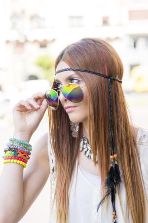mujer hippie: Portrait of beautiful young hippie woman looking over sunglasses. Foto de archivo