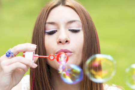 inflating: Closeup portrait of beautiful woman outdoor inflating colorful soap bubble.