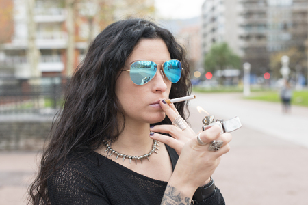 unhealthy lifestyle: Beautiful woman lighting cigarette, unhealthy lifestyle concept. Stock Photo