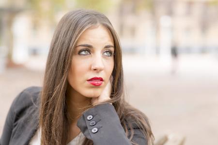 ojos verdes: Retrato de mujer joven con ojos verdes y mirada lejos de pensar, al aire libre.