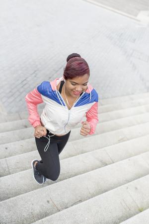 haciendo ejercicio: Mujer que hace ejercicio, correr arriba y abajo de la escalera.