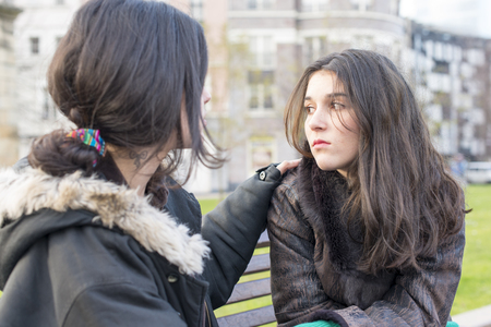 llorando mujer triste y amigo reconfortante en el parque.