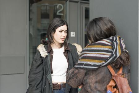 two friends talking: Two friends talking in the street. Stock Photo