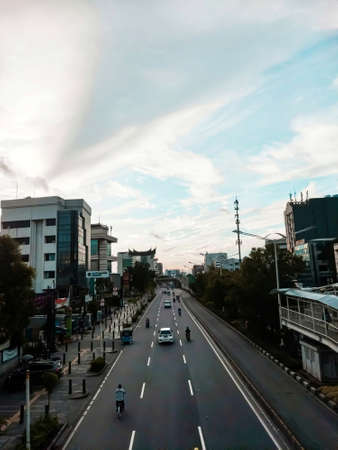 One highway in Jakarta, Indonesia, which is squeezed in a straight line by buildings, and crowded as usual in the morning, above is a stunning blue sky with bright white clouds, indicating the weather