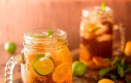 surrounded: Long island ice tea is served in mason jar. The brown drink has lemons sliced in it and it is surrounded with another jar  and lemons and mint leaves around it.