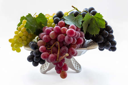 Black, red and yellow grapes on a white background.