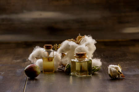 White cottons, cocoons and cottonseed oil in a bottle on a wooden floor.