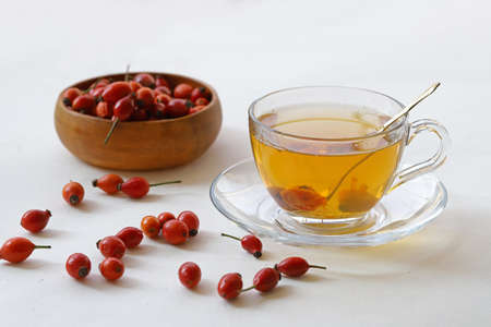 Rose hip herb and rose hip herbal tea in cup on white background.