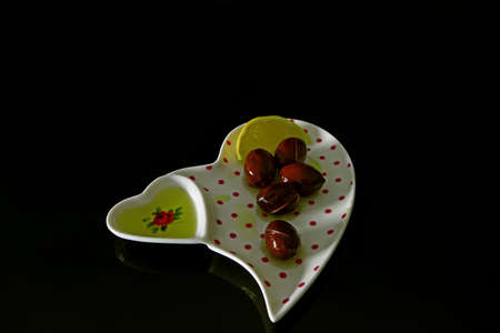 Olive oil in white plate on black background