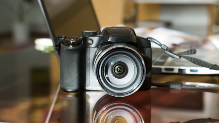represents: the camera costs on a glass table and is reflected from it, against the laptop. Represents work with photodrains of the house and on vacation.