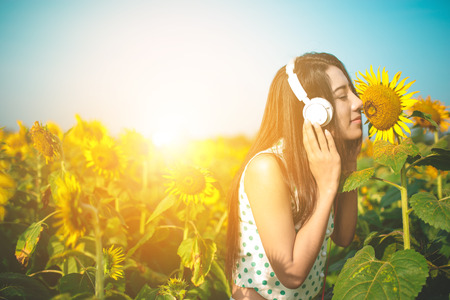 smells: Girl smells sunflower in field in the morning.