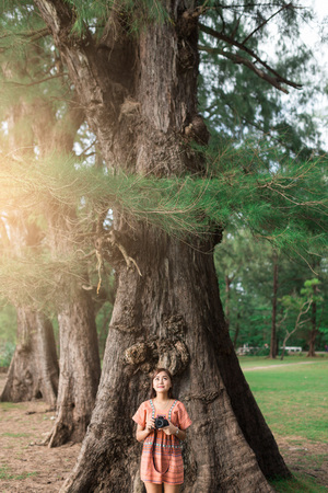 beatification: Beautiful girl holding camera and leaning against tree in the morning.