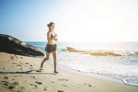 young fitness woman running on the beach in the morning. Stock Photo