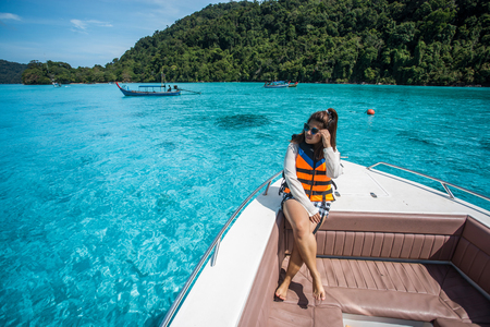 sit down: beautiful girl on the head speed boat and looking beautiful sea at Surin island, thailand Foto de archivo