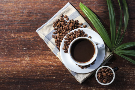 fragrant: coffee cup and beans on the wood background.