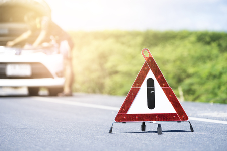 Emergency stop sign and man with broken car on the road Stockfoto