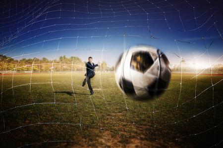 intend: asian businessman play football in the stadium foolball.