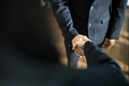 Business handshake and business people.soft focus,low light. handshake in office. success concept.