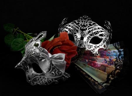 mascara de carnaval: Máscaras con rose.Silver máscaras de carnaval que ponen con abanico plegable y la rosa roja sobre fondo negro tela. Foto de archivo