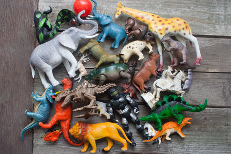 Bunch of toys table. Animals, dinosaurs & soldier bunch of toys laying on dirty old wooden table upper view. photo