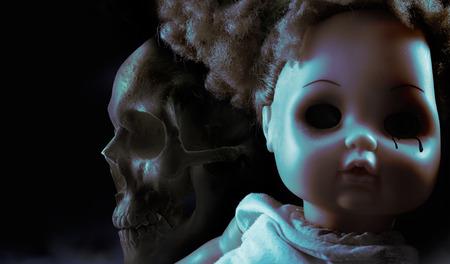 유령 신비 인형. 검은 눈물과 배경에 인간의 두개골 무서운 공포 플라스틱 인형 얼굴.