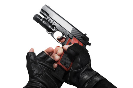 reloading: Hands in leather gloves reloading a gun clip first person view isolated photo.