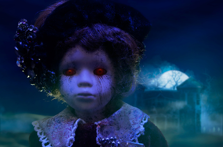 spooky: Horror doll with haunted house.Old mystical scary horror doll looking with red demonic eyes with haunted horror house.