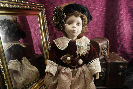 antique mirror: Retro fashioned porcelain doll. Composition of a retro fashioned porcelain doll in dress with border lace, jewelry  beret standing with antique mirror  chests.